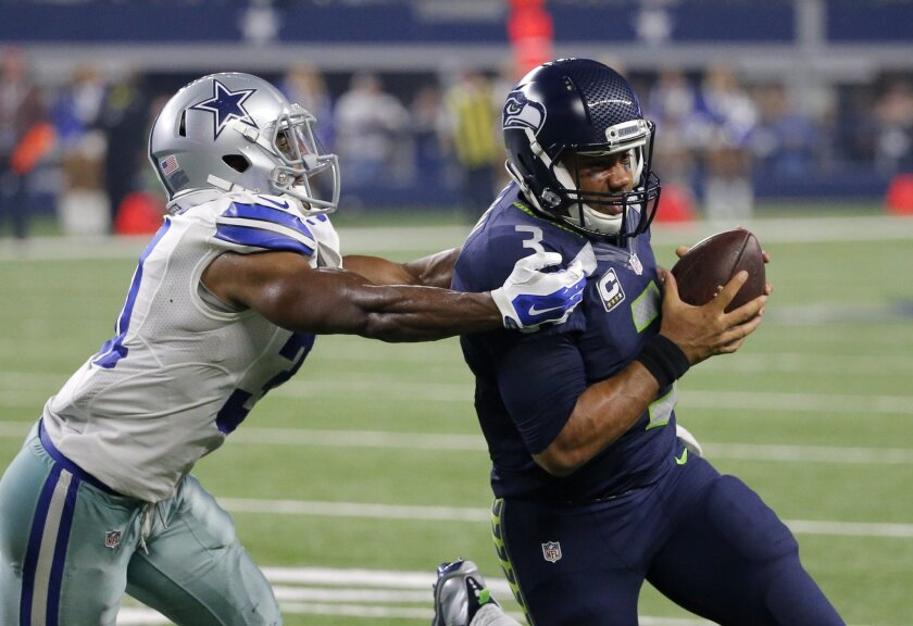 Dallas Cowboys cornerback Byron Jones (31) drives Seattle Seahawks' Russell Wilson (3) out of bounds after Wilson kept the ball for a run in the second half of an NFL football game Sunday, Nov. 1, 2015, in Arlington, Texas. (AP Photo/Brandon Wade)