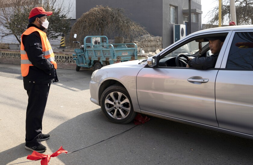 Fearing the spread of the coronavirus, men in the Chinese village of Xinzhuangzi are monitoring cars and people who want to enter.