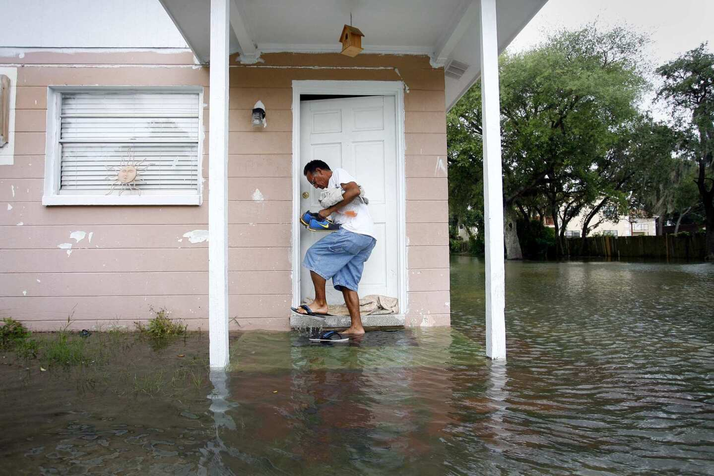 Mario Funes 61, of Tampa, leaves his apartment complex after rainwater from Tropical Storm Debby flooded the neighborhood.