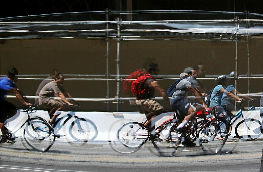 Bicyclists are reflected in the windows of a restaurant along Wilshire Boulevard in Los Angeles during the May 2009 CicLAvia festival.
