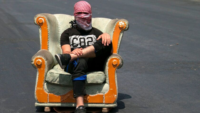 A Palestinian protester sits along the road during a demonstration at the Hawara checkpoint, south o