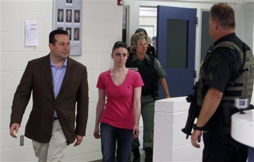 FILE -In this July 17, 2011 file photo, Casey Anthony, center, walks out of the Orange County Jail with her attorney Jose Baez, left,  during her release in Orlando, Fla.  Anthony comes out of seclusion for a meeting with the creditors in her bankruptcy case in Tampa Monday March 4, 2013.  (AP Phot