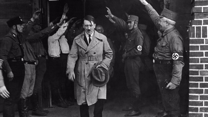 Adolf Hitler, leader of the National Socialists, emerges from the party's Munich headquarters on Dec