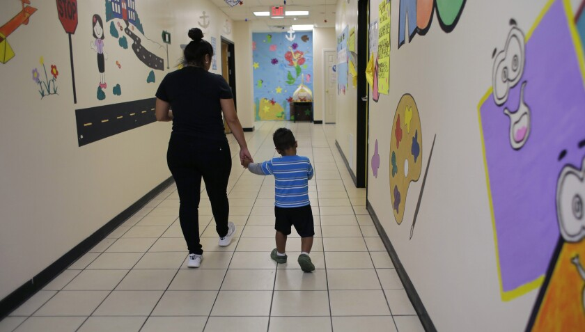 A migrant child and a caregiver at a 'tender age' facility
