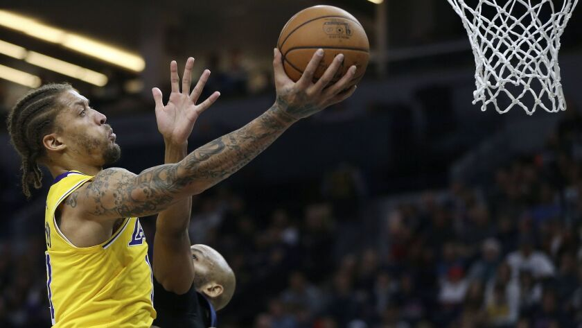 Los Angeles Lakers' Michael Beasley, left, shoots over the defense of Minnesota Timberwolves' Taj Gi