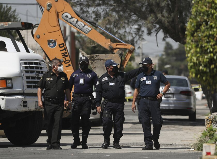 Police walk outside a house where bones were found under a floor in the Atizapan municipality of the State of Mexico May 20.