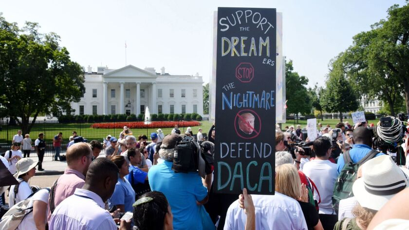 Protesters hold up signs during a rally supporting Deferred Action for Childhood Arrivals, or DACA, outside the White House.