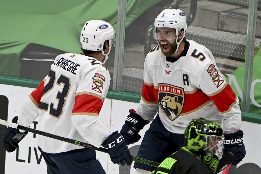 FILE - Florida Panthers defenseman Aaron Ekblad (5) and Florida Panthers center Carter Verhaeghe (23) celebrate Ekblad's winning goal as Dallas Stars goaltender Anton Khudobin, lower right, looks on during the overtime period of an NHL hockey game in Dallas, in this Saturday, March 27, 2021, file photo. The Florida Panthers won in overtime, 4-3. Ekblad, who broke his left leg midway through last season, says he will be full-go when the Panthers open training camp Thursday, Sept. 23. (AP Photo/Matt Strasen, File)