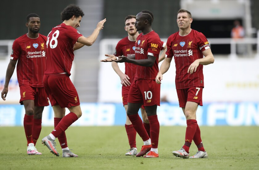 Liverpool's Sadio Mane, center, celebrates with teammates after scoring his side's third goal during the English Premier League soccer match between Newcastle and Liverpool at St. James' Park in Newcastle, England, Sunday, July 26, 2020. (Owen Humphreys, Pool via AP)