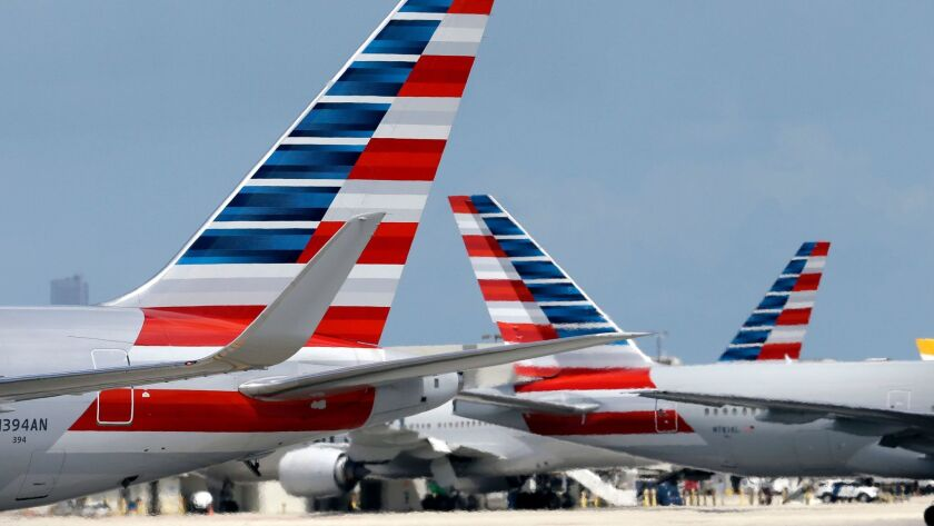 American Airlines jets taxi at Miami International Airport. A merger with US Airways made American Airlines the world's largest carrier. A judge has refused to dismiss an antitrust lawsuit against the nation's biggest airlines.