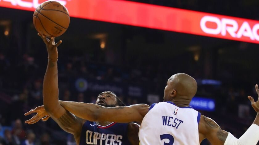 Clippers' DeAndre Jordan puts up a shot despite getting hit on the arm by Golden State's David West in the first half.