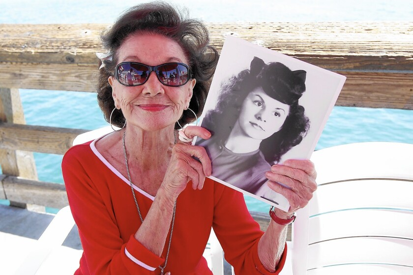 Ruby Cavanaugh, whose son named the Ruby's Diner chain after her, holds a photo of herself as a young woman.