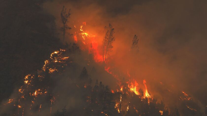 The deadly Camp fire burns in Northern California in November. State investigators are looking at a utility transmission line as a possible ignition point for the fire.