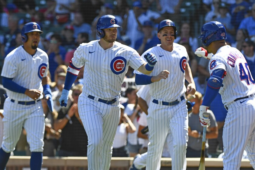 Chicago Cubs' Ian Happ, second from left, is congratulated by teammate Willson Contreras (40) after hitting a three-run home run during the first inning of a baseball game against the Cincinnati Reds, Monday, Sept. 6, 2021, in Chicago. (AP Photo/Matt Marton)