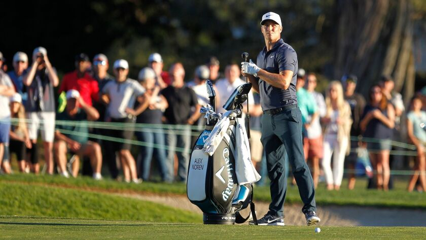 Alex Noren changes clubs as he looks at the wind during the first playoff hole during the Farmers Insurance Open.