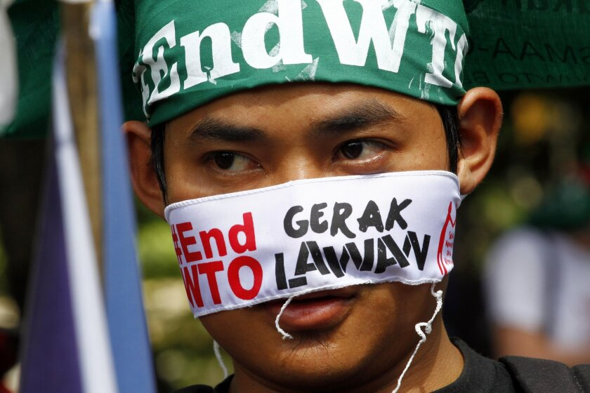 """An activist wraps his face during a protest against the World Trade Organization meeting in Bali, Indonesia on Tuesday, Dec. 3, 2013. Indonesia is hosting the World Trade Organization Ministerial Conference from Dec. 3 - 6. The word """"Gerak"""" means Movement.(AP Photo/Firdia Lisnawati)"""