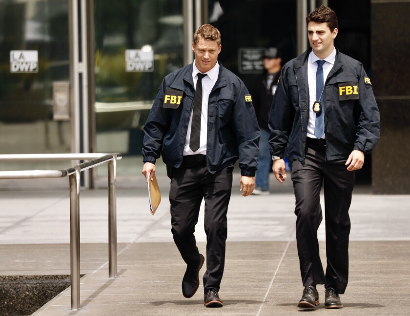 FBI agents leave the downtown headquarters of the Los Angeles Department of Water and Power after serving a search warrant on Monday. Authorities have declined to discuss the nature of the investigation that led to the raid.