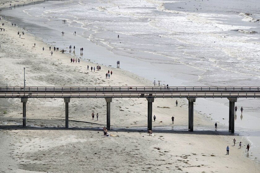 People walk along La Jolla Shores on Thursday. Gov. Gavin Newsom announced that San Diego County beaches would be allowed to remain open.