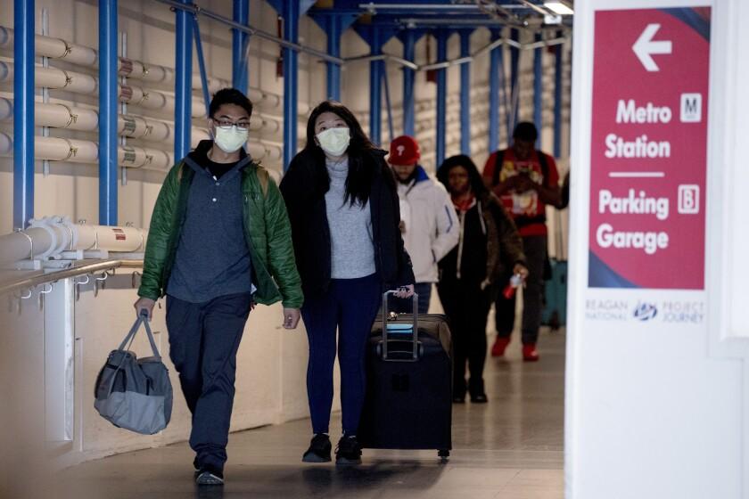 People wearing a masks walk through a terminal at Ronald Reagan Washington National Airport, Monday, March 16, 2020, in Arlington, Va. (AP Photo/Andrew Harnik)