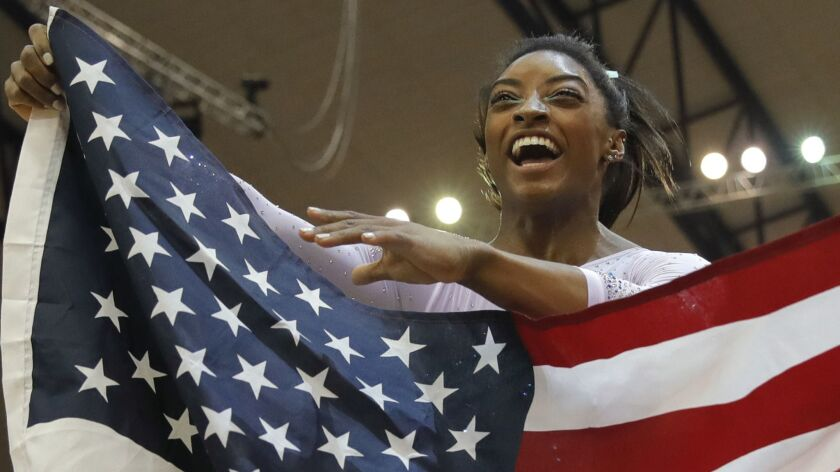 Simone Biles celebrates with the U.S. flag after winning her fourth world all-around championship.