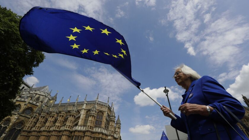 A pro-EU demonstrator waves a flag outside Parliament in London on Wednesday. The British government is bracing for more bruising debate on its key Brexit bill after being forced to give ground to pro-EU lawmakers to avoid defeat.
