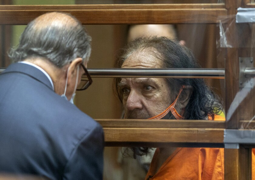 Adult film star Ron Jeremy, wearing a prison jumpsuit, talks with his attorney Stuart Goldfarb during his arraignment