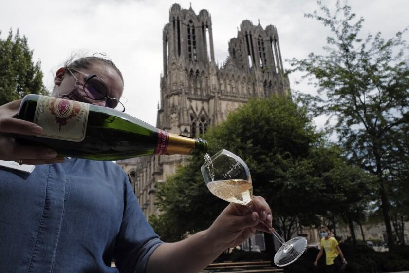 Una camarera sirve champaña en el restaurante La Grande Georgette frente a la catedral de Reims