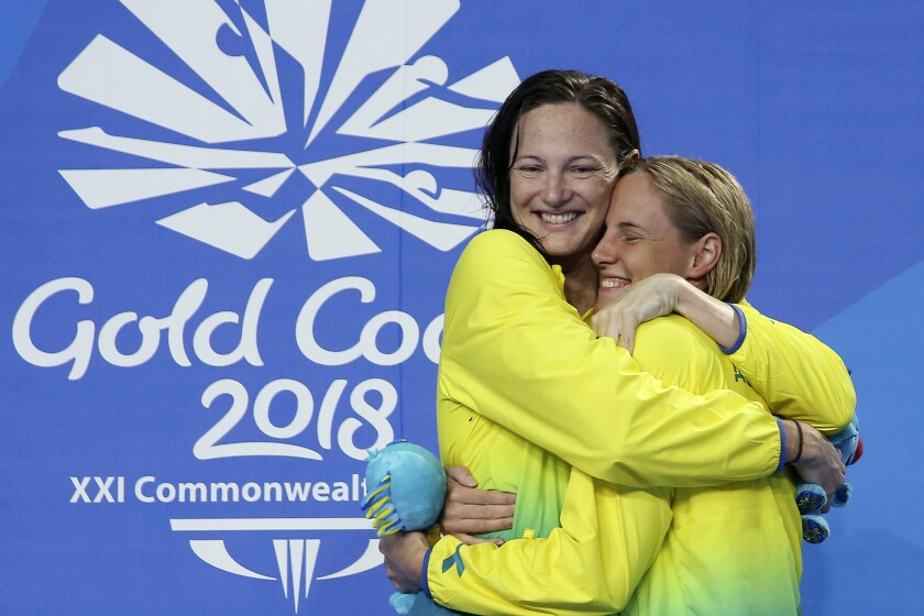 FILE - In this April 9, 2018, file photo, Australia's swimming sisters Bronte Campbell, right, and Cate Campbell hug during the medal ceremony for the women's 100m freestyle final at Aquatic Centre during the 2018 Commonwealth Games on the Gold Coast, Australia. Even before the coronavirus pandemic, the Australian swimming siblings have had their share of health concerns. (AP Photo/Rick Rycroft, File)