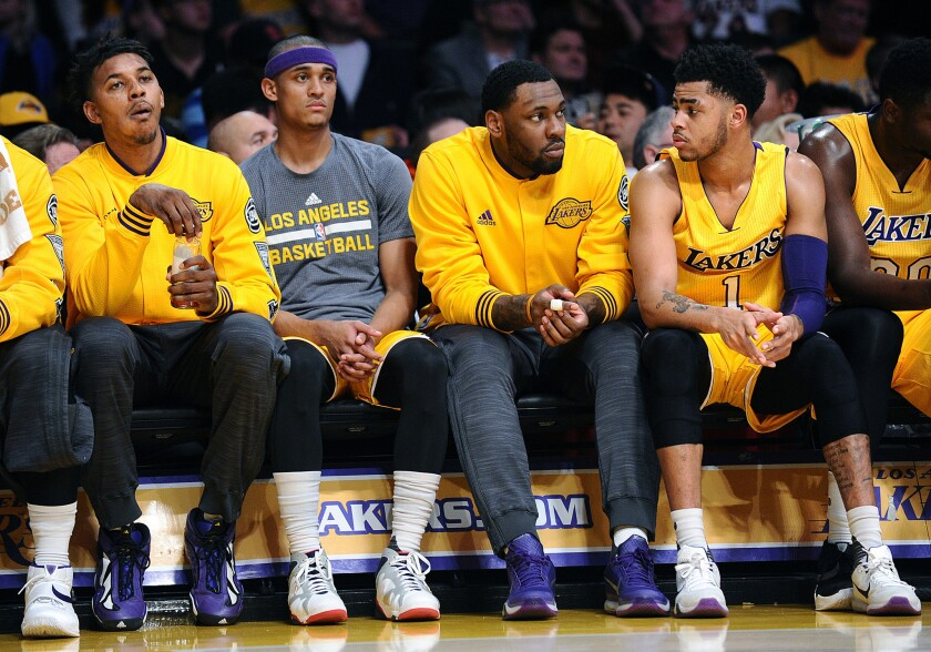 Lakers forward Nick Young, far left, and teamate D'Angelo Russell, right, sit on the bench apart from each other during a game against the Heat.