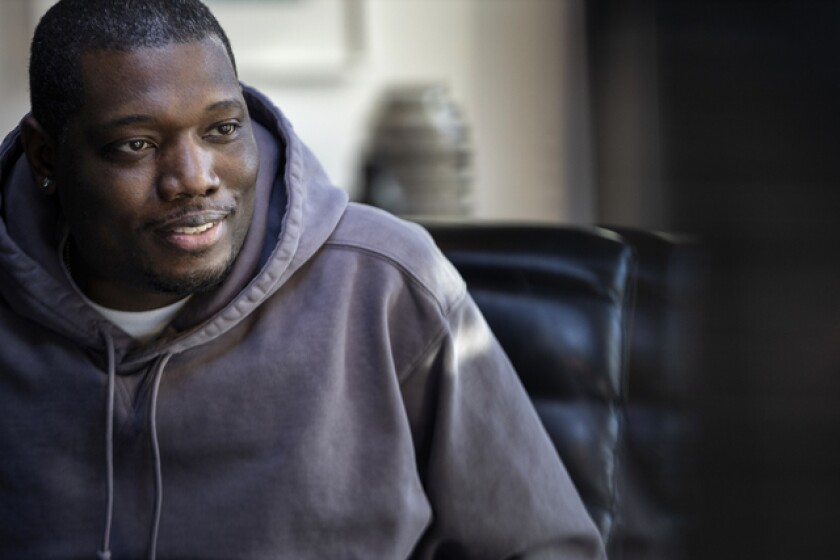 Comedian Michael Che smiling in a purple hoodie