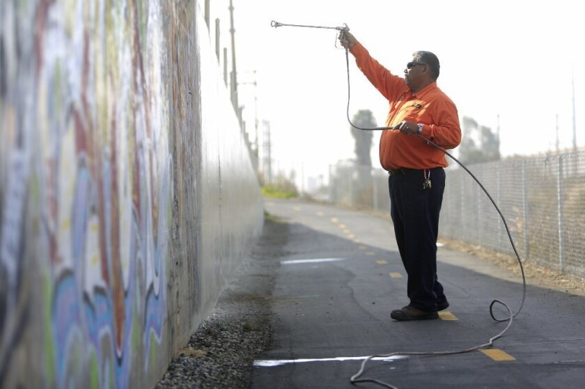 Gilbert Ponce walks toward another panel of graffiti on a retaining wall along a portion of the Bayshore Bikeway in Chula Vista.