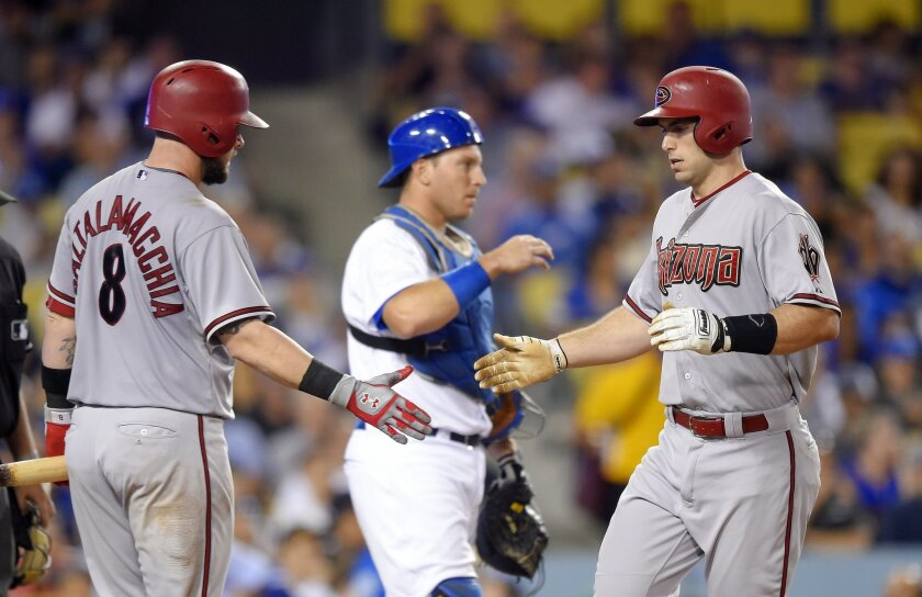 Arizona Diamondbacks' Paul Goldschmidt, right, is congratulated by Jarrod Saltalamacchia, left, as Los Angeles Dodgers catcher A.J. Ellis stands at the plate after hitting a solo home run during the seventh inning of a baseball game, Tuesday, Sept. 22, 2015, in Los Angeles. (AP Photo/Mark J. Terrill)