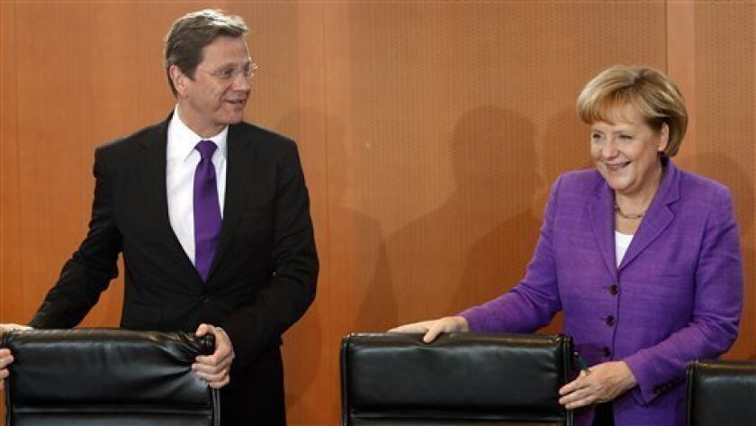 German Vice-Chancellor and foreign minister Guido Westerwelle, left, and German Chancellor Angela Merkel, right, arrive for a meeting of the cabinet at the chancellery in Berlin, Germany, Wednesday, June 2, 2010. (AP Photo/Michael Sohn)