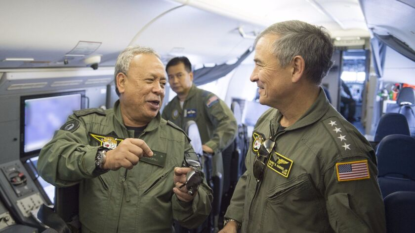 Gen. Zulkifeli Mohd Zin of Malaysia, left, talks with Adm. Harry Harris of U.S. Pacific Command on April 21 during a flight above the Strait of Malacca.
