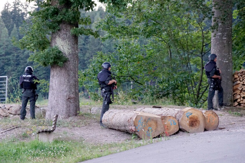 Police officers stay outside a wooded area on a road near Oppenau, Germany, Monday, July 13, 2020. Authorities in Germany say they have deployed hundreds of police in the hunt for a 31-year-old man who disarmed four officers at gunpoint on Sunday, July 12, 2020. (Sven Kohls/dpa via AP)