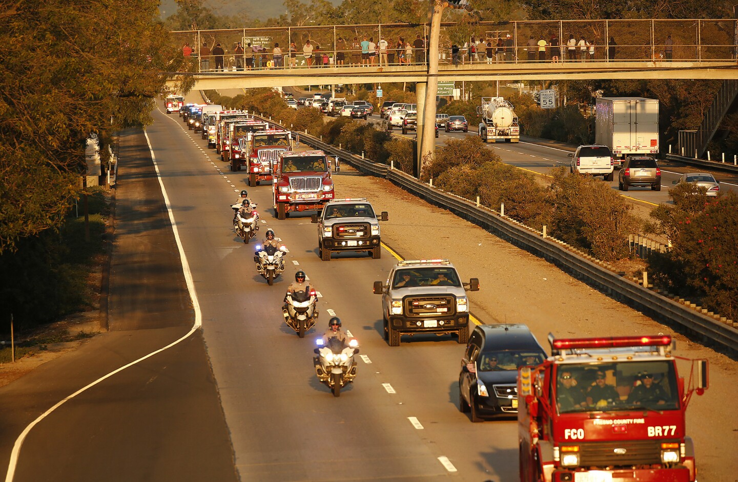 A motorcade proceeds down Highway 126 in Santa Paula carrying the body of firefighter Cory Iverson, 32, who died Thursday morning while battling the Thomas fire outside Fillmore.