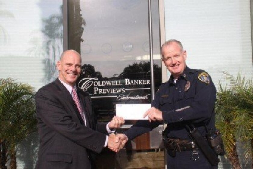 Jeffrey Nunn,  branch manager of Coldwell Banker Residential Brokerage in La Jolla,  presents a check for $500 to Captain Ahearn for the repairs. Courtesy Nancy Gardner