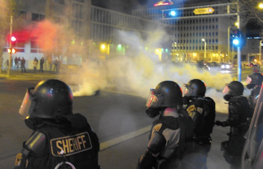 Riot police fire tear gas toward protesters gathered in downtown Albuquerque after the March 2014 police killing of James Boyd, a mentally ill homeless man.
