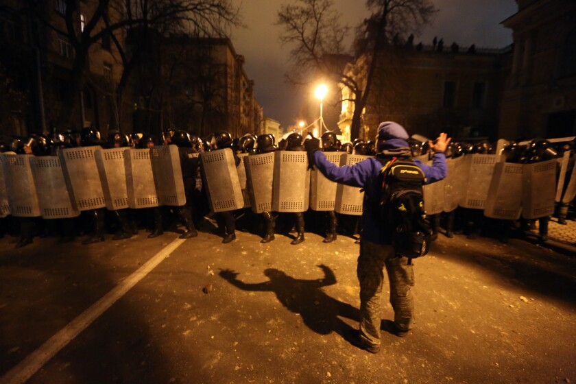 A protester faces riot troops near the Presidential Administration building in downtown Kiev on Sunday evening.