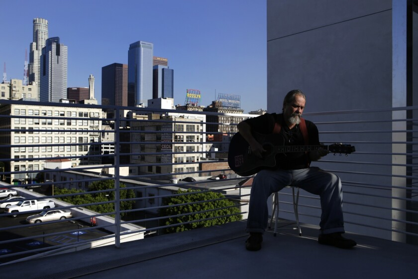 Bill Fisher, 61, has a view of the downtown L.A. skyline from outside his apartment in a new complex at 6th Street and Maple Avenue in skid row.