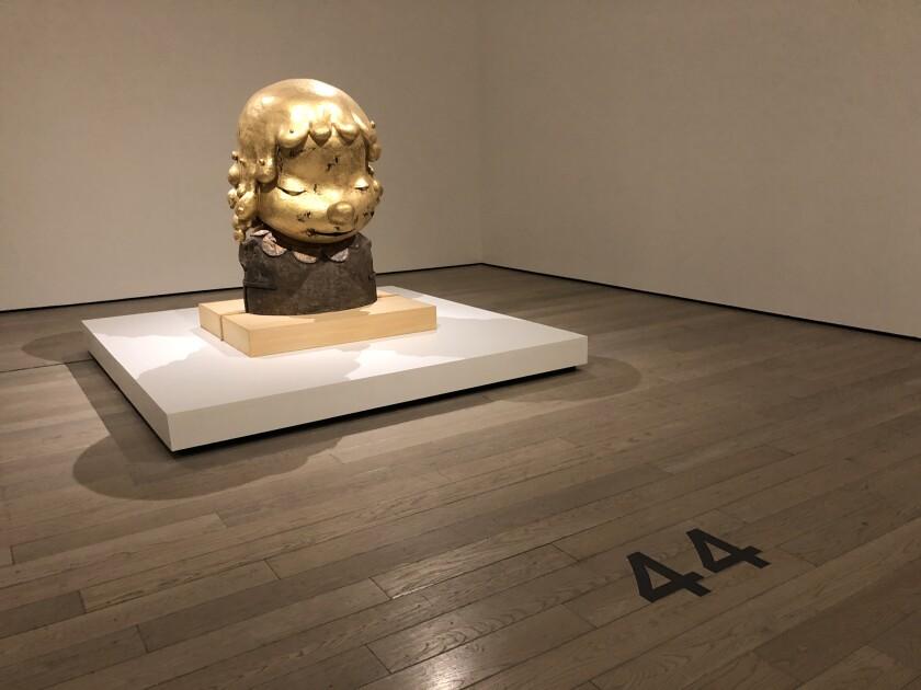 A golden sculpture in a gallery.
