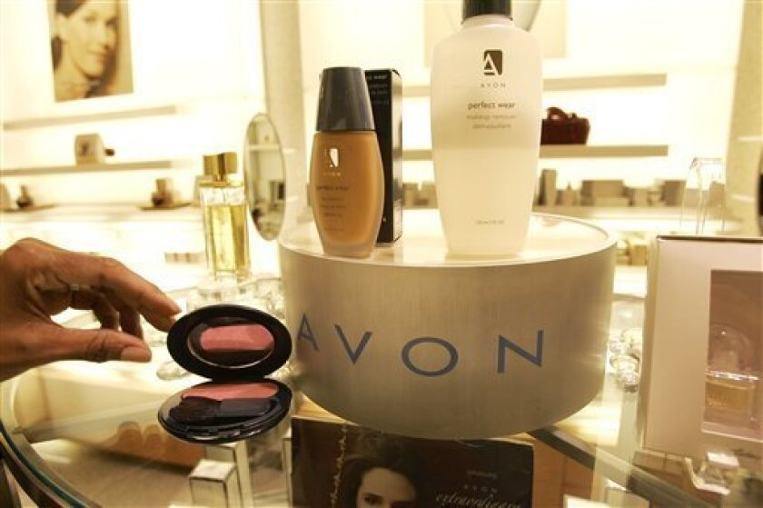 FILE - In this file photo made Nov. 15, 2005, a saleswoman, who did not give her name, places items for a picture on display in an Avon store in New York. Struggling Avon Products Inc. is rejecting a buyout offer worth about $10 billion from beauty company Coty Inc., as Coty went public with the bid Monday, April 2, 2012. (AP Photo/Gregory Bull, File)
