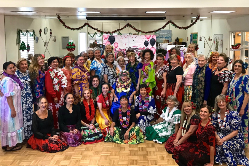 """Christinia Pualani Lee retired at 101 years of age, after teaching hula classes at the Carlsbad Senior Center for the past 24 years. The Encinitas great great-grandmother, known as """"the hula lady,"""" has led Hawaiian dance classes twice a week at the Carlsbad Senior Center, Lee, who was a volunteer, started the class in spring of 1995 when she was in her late 70s, about six months after her husband died of cancer. Lee looked at hula as a form of storytelling about the history of the Hawaiian islands. She talked about the spiritual part of hula and often said that the dance has to come from the heart. Pictured is Christinia Pualani Lee, center seated in chair, surrounded by her students at her retirement party. Photo by Kevin Cotton."""