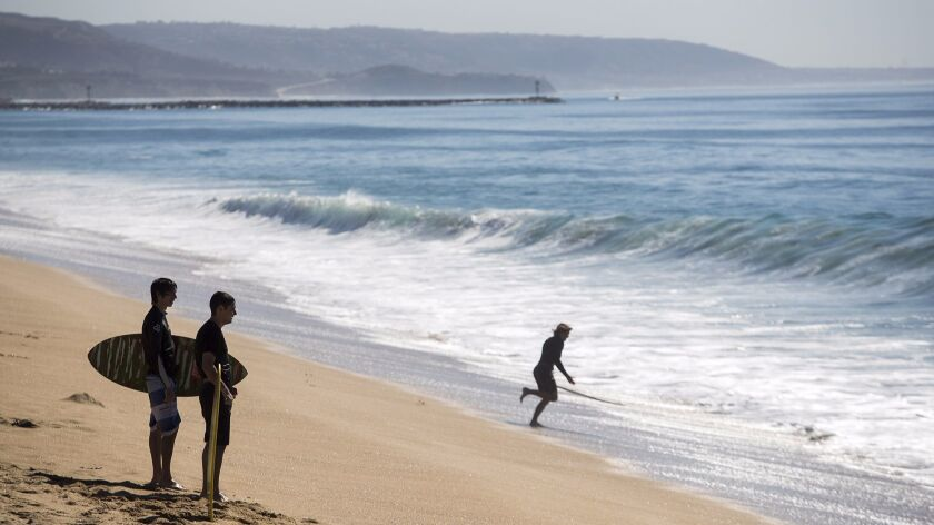 Skimboarders look for waves Tuesday on an unusually hot day in Newport Beach. Temperatures reached more than 100 degrees in the city, breaking the record of 85 degrees for the date, set in 1965.