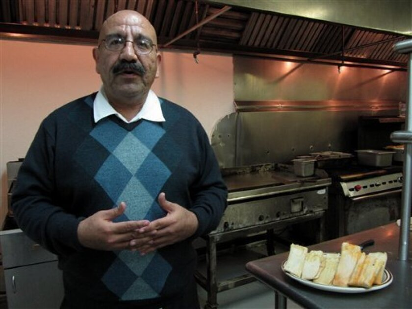 Jaime O. Perez poses with a plate of homemade tamales in an El Paso, Texas restaurant on Friday, Dec. 11. Perez is hoping to sell tamales to fund a run for U.S. Congress. (AP Photo/Alicia A. Caldwell)