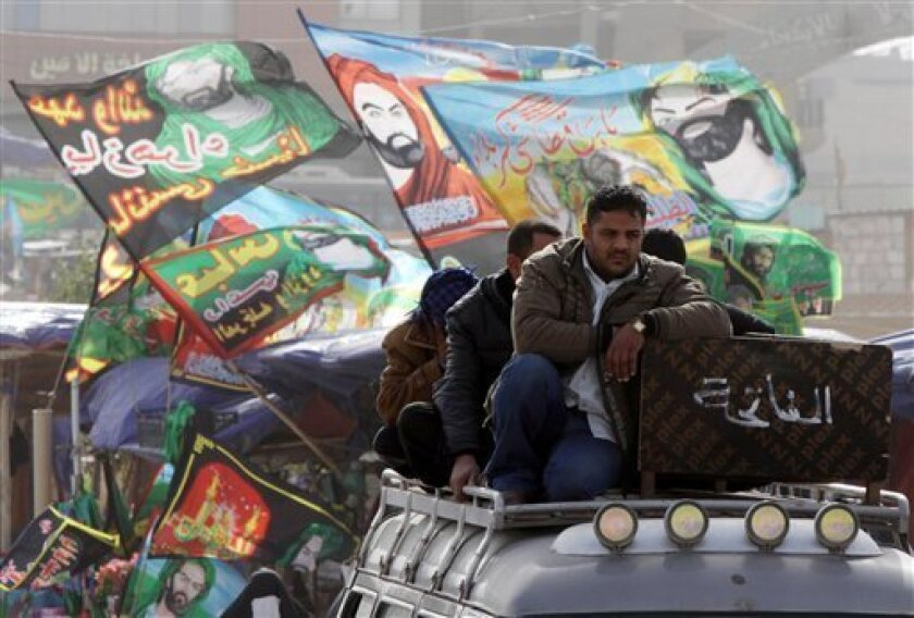 Religious flags of Shiite Imams waves while relative of Qssim Abbas, 48, who was killed in a bomb attack take his body for burial in the Shiite holy city of Najaf, 160 kilometers (100 miles) south of Baghdad, Iraq, Friday, Jan. 6, 2012. On Thursday a series of bombings targeting members of Iraq's Shiite Muslim majority killing and injuring dozens of Iraqis, police said. (AP Photo/Alaa al-Marjani)