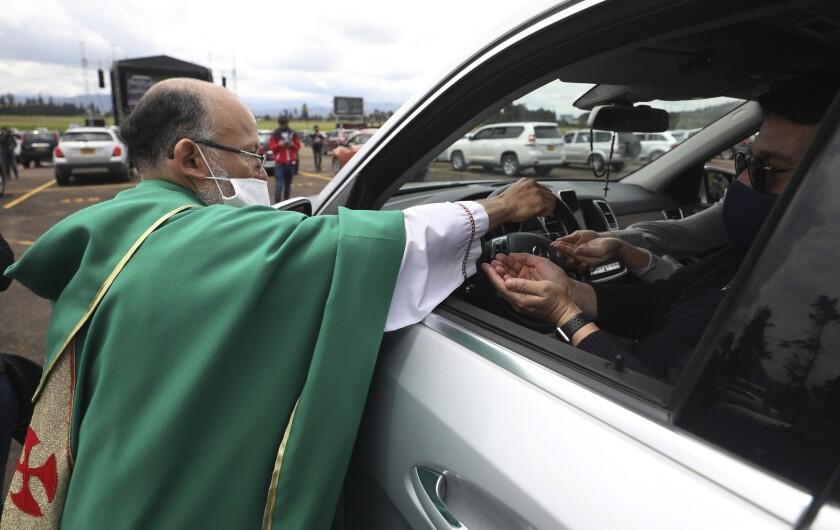 El sacerdote católico Luis Carlos Ayala, con una mascarilla para protegerse del coronavirus,
