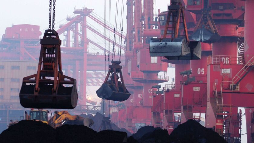 Machines move imported iron ore in Rizhao, China, on June 6, 2015.