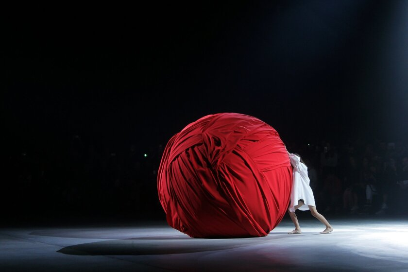 A model pushes a giant ball during Jacquemus' Spring-Summer 2016 ready-to-wear fashion collection, in Paris, Tuesday, Sept. 29, 2015. (AP Photo/Thibault Camus)