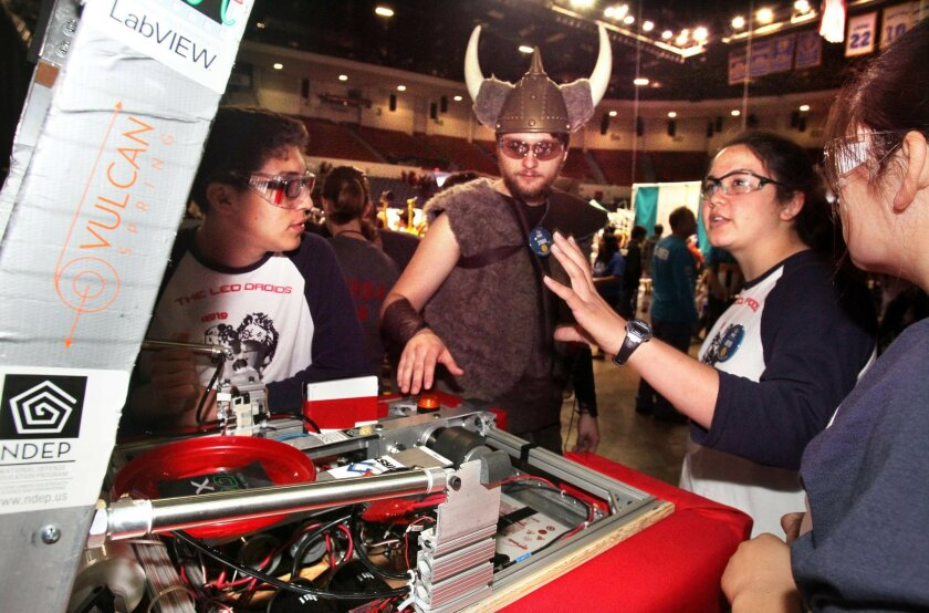 First Robotics Competition Game at the Valley View Casino Center (sports arena)- George Brabon, in horned headgear of La Jolla High, speaks with members of the Leo Droids, a composite team that's about to compete, LtoR: Adrian Maya, (Brabon), Miranda Ng and her sister Katherine Ng.